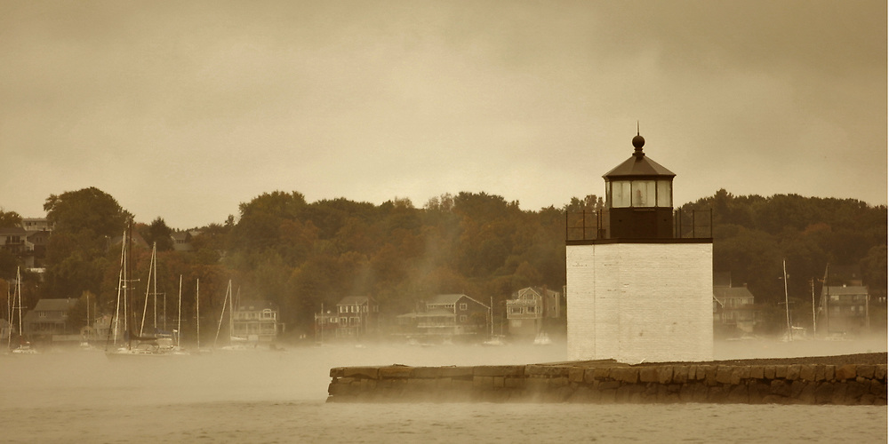 Fog envelopes Derby Pier Light in Salem harbor.