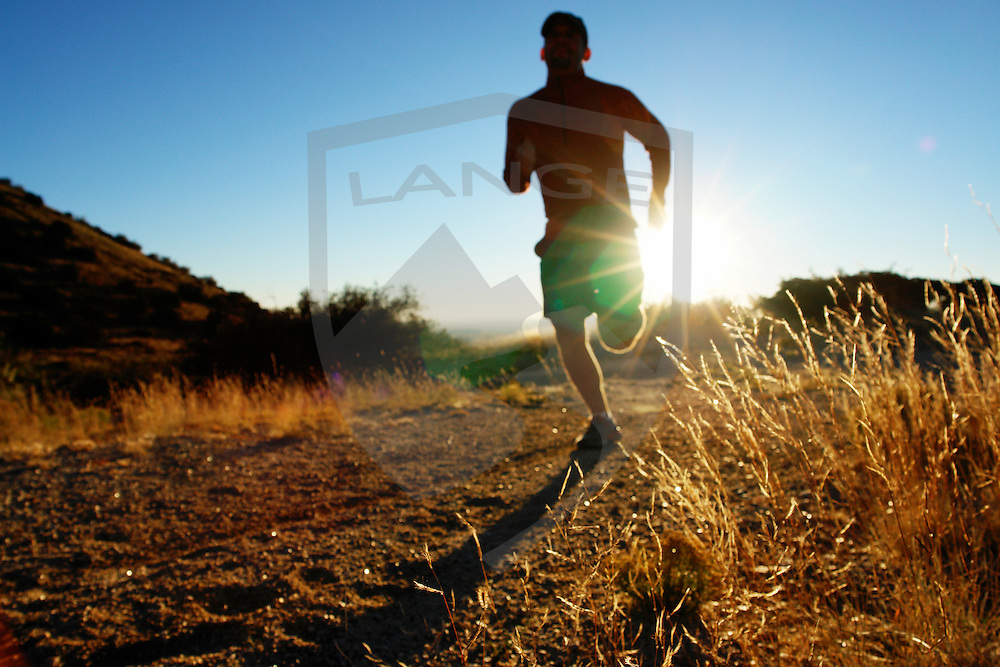 the sandia mountains of albuquerque new mexico offer myriad outdoor sports and recreation opportunities, including trail running in the foothills.  here, a trail runner man cross country runs with sun lens flare in the landscape, defocused 3