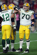 Green Bay Packers guard T.J. Lang (70) celebrates with Green Bay Packers quarterback Aaron Rodgers (12) after a third quarter touchdown gives the Packers a 13-7 lead during the NFL NFC Divisional round playoff football game against the Arizona Cardinals on Saturday, Jan. 16, 2016 in Glendale, Ariz. The Cardinals won the game in overtime 26-20. (©Paul Anthony Spinelli)