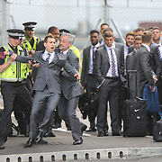 PIC BY GEOFF ROBINSON PHOTOGRAPHY 07976 880732.<br /> <br />  PIC SHOWS   COMEDIAN SIMON BRODKIN BEING TAKEN AWAY BY POLICE AFTER GETTING PAST  SECURITY AND TALKING TO THE ENGLAND TEAM WHEN THEY ARRIVED AT LUTON AIRPORT ON SUNDAY MAY 1ST.  <br />  <br /> Comedian Simon Brodkin tried to join the England football team today (Sun) as they flew from Luton Airport to Miami for the start of their World Cup training.<br /> <br /> The players, including Steven Gerrard, looked on in bemusement as Brodkin, who is best known for his comic creation Lee Nelson, pushed past the security guards.<br /> <br /> Brodkin, who was in the guise of footballer Jason Bent, a character from his BBC Three series Lee Nelson's Well Funny People, was wearing an identical suit and tie to the team.<br /> <br /> He waved his passport at the security guards as the players made their way from a coach to a private hangar ready to board the plane.<br /> <br /> He was then seen asking Steven Gerrard why he hadn't been picked to represent England in the World Cup, which kicks off on Thursday, June 12.<br /> <br /> The players saw the funny side of the comic gaff, but police and security staff quickly swooped on him and he was escorted away for questioning.<br /> <br /> SEE COPY CATCHLINE Comedian tries to join England squad