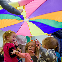 Samaria Sandlin, center, and other children play a parachute game during Toddler Time at the Gallup Children's Library Wednesday.