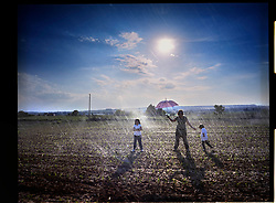 2012.Binefar, Huesca. Laura Herbera, a farmer with her children Romeral and Marco, in an alfalfa field.© Carmen Secanella