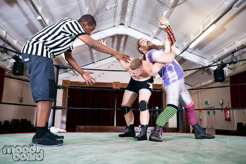 Full-length of wrestlers fighting while referee gesturing in ring
