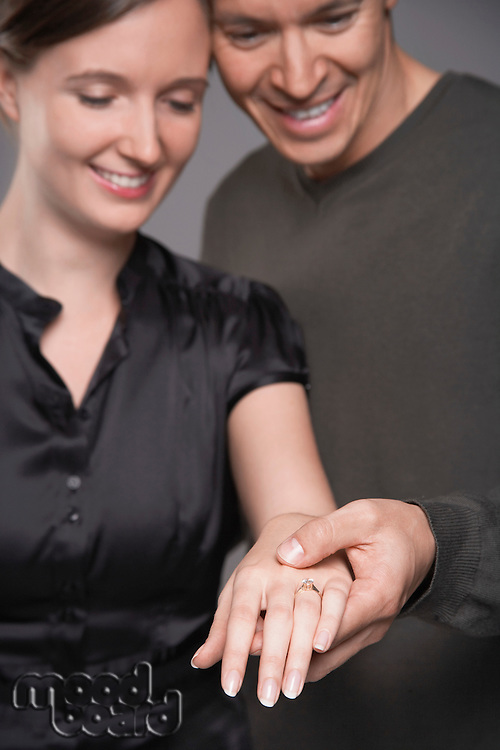 Couple looking at engagement ring on woman's hand