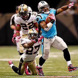 October 3, 2010; New Orleans, LA, USA; Carolina Panthers running back DeAngelo Williams (34) escapes a tackle by New Orleans Saints cornerback Malcolm Jenkins (27) on a touchdown run during the third quarter at the Louisiana Superdome. Mandatory Credit: Derick E. Hingle