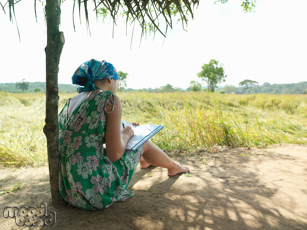 Young woman sitting in shade writing back view