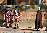 Actors play a woman in brown cape and two American militia carrying drum and fife outside of the Capitol building at Colonial Williamsburg, Virginia. Colonial Williamsburg is the historic district of the independent city of Williamsburg, Virginia, which was colonial Virginia's capital from 1699 to 1780, and a center of education and culture.