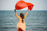 Girl waving red scarf by the sea