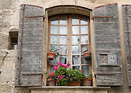 An old window with wooden shutters in Arles, France