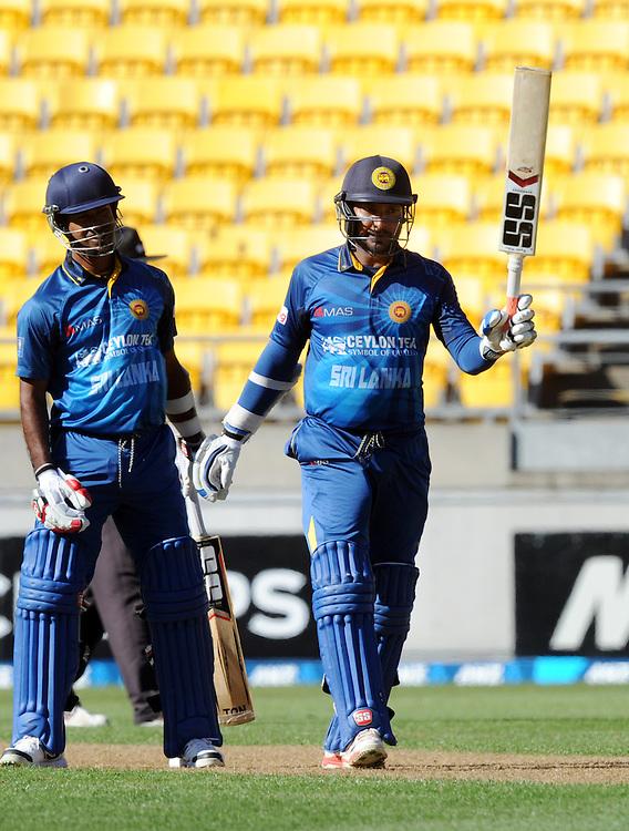 Sri Lanka's Kumar Sangakkara, right, watched by Nuwan Kulasekera signals his century against New Zealand in the 7th One Day International cricket match at Westpac Stadium, New Zealand, Sunday, January 29, 2015. Credit:SNPA / Ross Setford