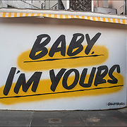 Graffiti artist and muralist Baron Von Fancy &quot;Baby I'm Yours&quot; street art. <br /> <br /> I Feel You Baby is logo for Baby Brasa,a Peruvian rotisserie restaurant.