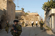 Jewish worshipers arriving in Hebron by foot, escorted by the Israeli military, to participate in the Haye Sarah Shabbat. Thousands of Jews, and a large number of settlers come to Hebron for the Haye Sarah during which the story of Abraham purchasing the land and cave on which stands the Tomb of the Patriarchs is read. Some six hundred Jews live in the heart of Hebron's old city surrounded by over 160,000 Palestinian inhabitants..Hebron, Israel. 02/11/2007.Photo © J.B. Russell/Blue Press