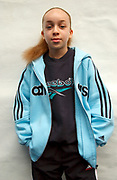 Portrait of young girl with bright blue striped Adidas jacket and Reebok sweater underneath, London, 2000's