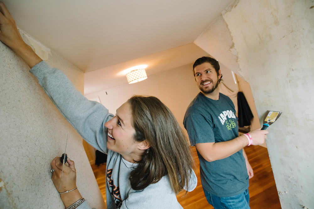 A young couple strip wallpaper in their new Swampscott, MA, home for the Mass Housing Annual Report.