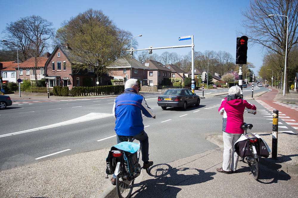 In Ede staat een ouder echtpaar met een elektrische fiets te wachten bij een verkeerslicht.<br /> <br /> In Ede an older couple with e-bikes is waiting for a traffic light.