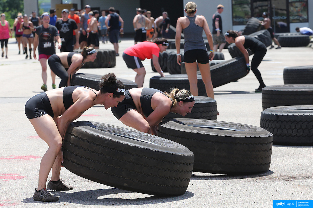 Competitors in action at the tyre lift obstacle during the Reebok Spartan Race. Mohegan Sun, Uncasville, Connecticut, USA. 28th June 2014. Photo Tim Clayton