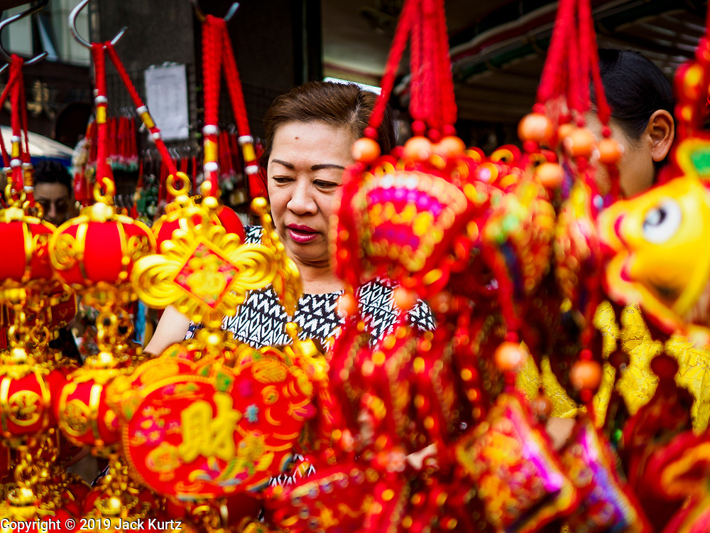 11 JANUARY 2019 - BANGKOK, THAILAND: A woman shops for Chinese New Year decorations at a street stall in Bangkok's Chinatown. About 14% of Thais are of Chinese ancestory and Lunar New Year is widely celebrated in Thailand. Chinese New Year celebrations in Bangkok start on February 4, 2019. The coming year will be the Year of the Pig in the Chinese zodiac.        PHOTO BY JACK KURTZ