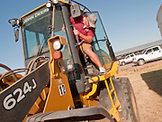 31 JULY 2009 --  BUCKEYE, AZ: Zachary Vanderham (CQ) from Texas, climbs out of a loader before bidding at the auction on the former Pylman Dairy Farm in Buckeye. The auction was handled by Overland Stockyards from Hanford, CA. The Arizona dairy industry is struggling to survive the worst milk economy some have ever seen. Due to the global recession, overseas demand for Arizona dairy products has plummeted, forcing prices down while production costs have stayed stable or gone up. For every $1 dairymen earn from milk sales, it cost them $1.50 to produce the milk. Photo by Jack Kurtz