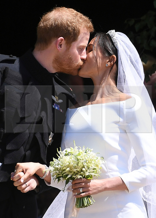 © Licensed to London News Pictures. 19/05/2018. London, UK.  Prince Harry, The Duke of Sussex and Meghan Markle, The Duchess of Sussex are pictured kissing as they leave St George's Chapel in Windsor Castle following a wedding ceremony. Photo credit: LNP