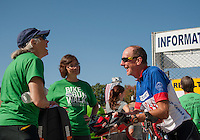 Sara Rosenblum and Diane Hanley greet Mike Ware after he finishes the 15 mile Take The Bay ride during Saturday's WOW Fest at Laconia Athletic and Swim Club.   (Karen Bobotas/for the Laconia Daily Sun)