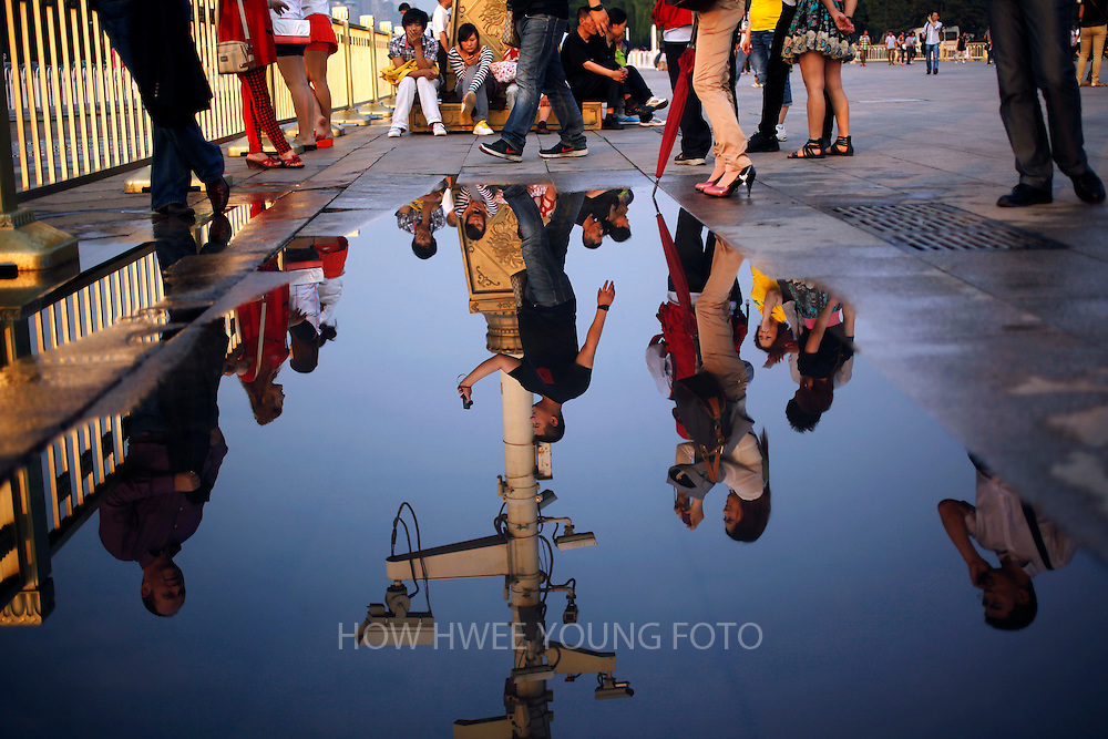 epa03247654 Visitors are reflected in a puddle in Tiananmen Square on the eve of the 23rd anniversary of the Tiananmen Square massacre in Beijing, China, 03 June 2012. Hundreds of students died in the Tiananmen Square area of Beijing in June 1989 when the Chinese government sent in troops to crush a pro-democracy uprising and preserve one-party rule in China.  EPA/HOW HWEE YOUNG