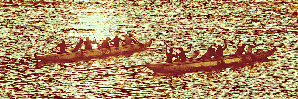 Outrigger canoe race at sunset