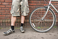 Low section of biker standing with bicycle