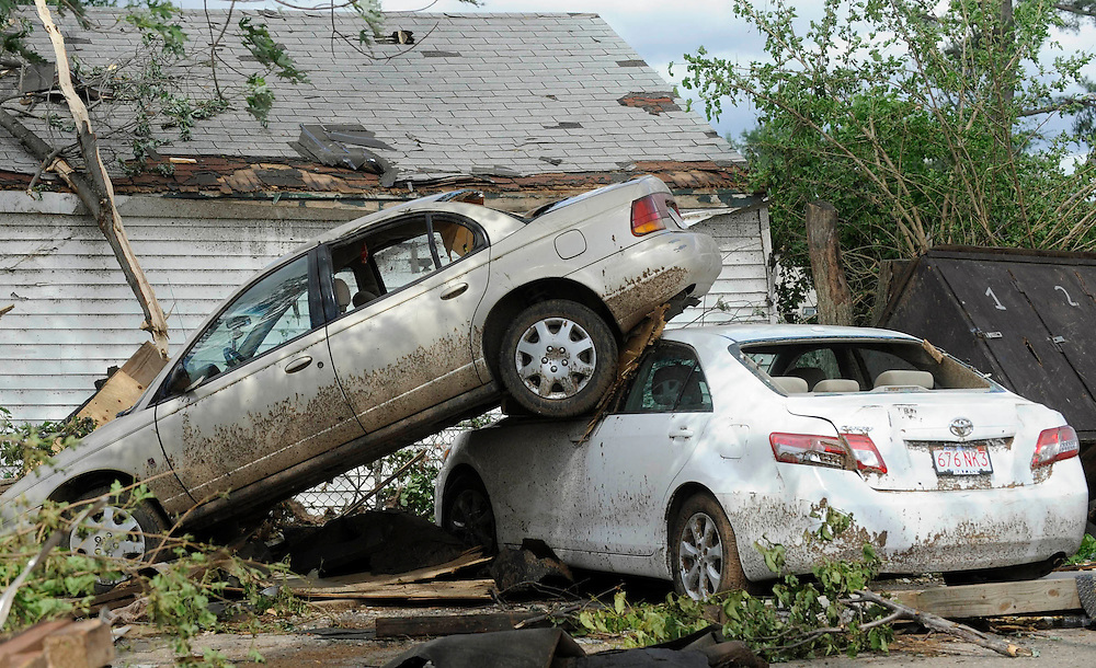 A car is lifted ontop another from a tornado the day before in West Springfield, Mass., Thursday, June 2, 2011.  (AP Photo/Jessica Hill)