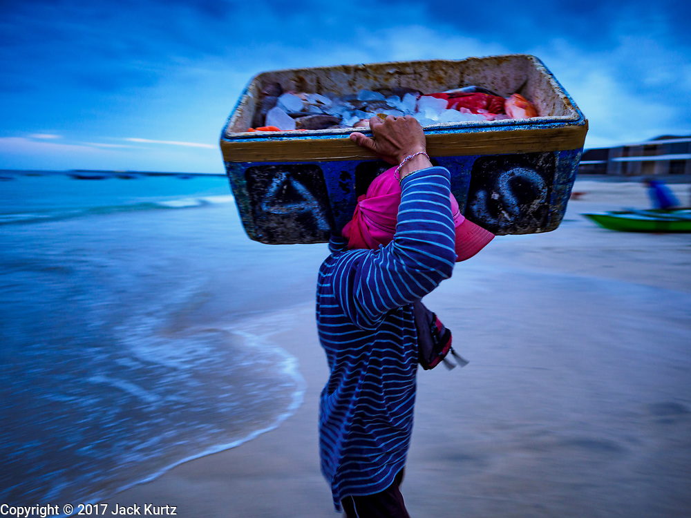 03 AUGUST 2017 - KUTA, BALI, INDONESIA: A fish market worker carries an ice chest of fish from a canoe to the market on Jimbrana Beach in Kuta. The beach is close to the airport and a short drive from other beaches in southeast Bali. Jimbrana was originally a fishing village with a busy local market. About 25 years ago, developers started building restaurants and hotels along the beach and land prices are rising. The new emphasis on tourism is changing the nature of the area but the fishermen are still busy very early in the morning.     PHOTO BY JACK KURTZ