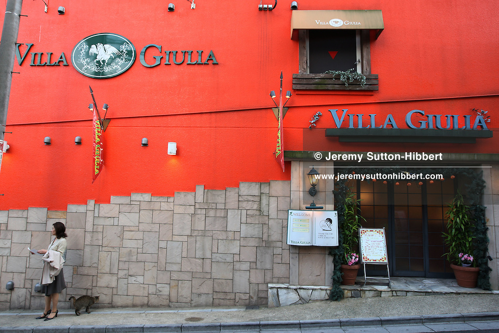 A woman awaits a rendezvous with someone outside the 'Villa Giulia' love hotel, in the Love hotels district in the hillside streets of Shibuya district, Tokyo, Japan, Monday 22nd Oct, 2007.