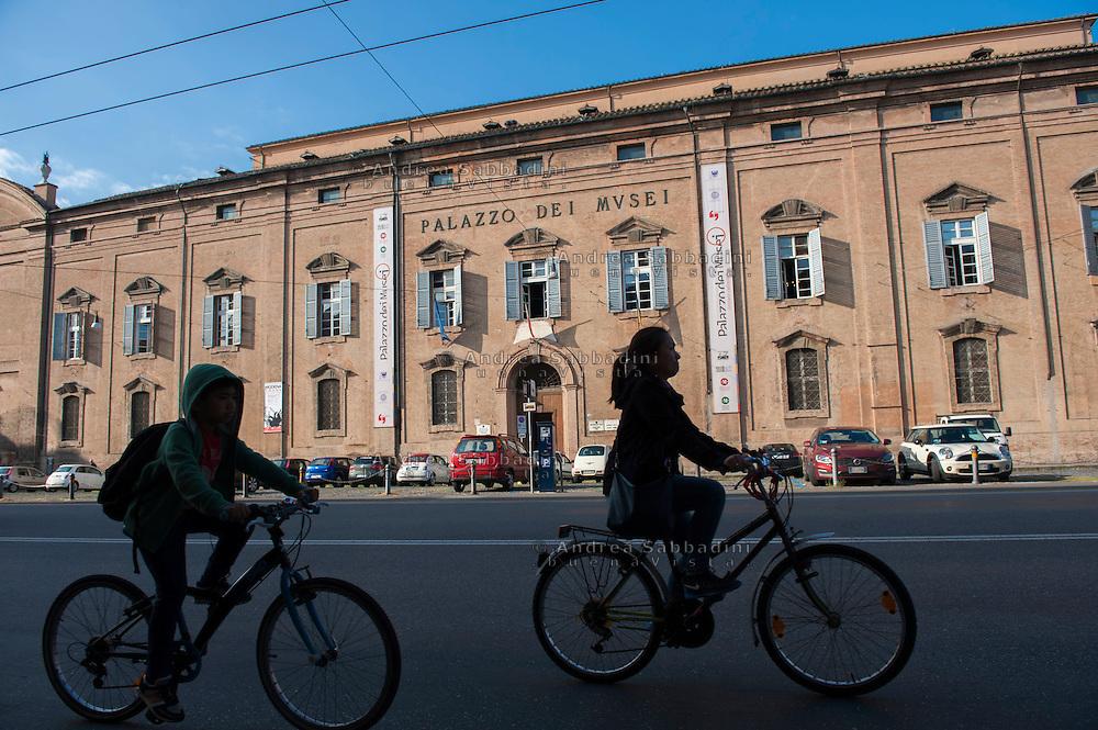 Modena, 17/05/2016: passanti in bicicletta davanti al palazzo dei Musei.<br /> &copy;Andrea Sabbadini
