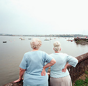 Holidaying ladies in blue look out across the harbour at Monkstown, Co Cork, Ireland, towards the local Pfizer factory that manufactures Viagra.