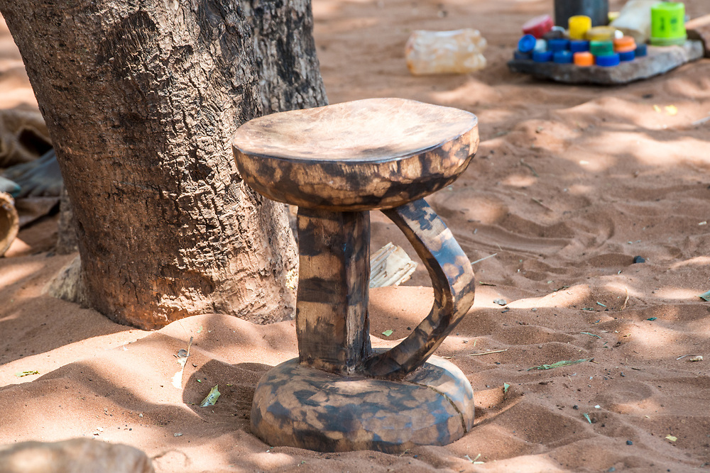 Hand craved stool sits on top of sandy ground, Mukuni Village, Zambia
