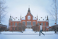 A young man walks by the city hall (Stadshus) in Umeå, Sweden