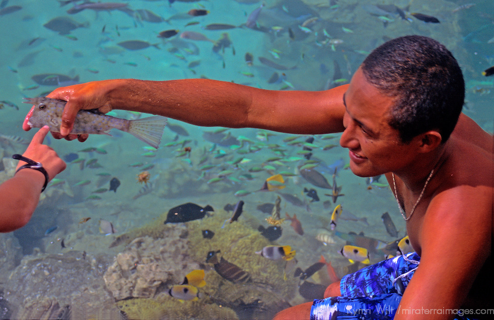 Oceania, South Pacific, French Polynesia, Tahiti. Polynesian sharing knowledge about tropical fish species.