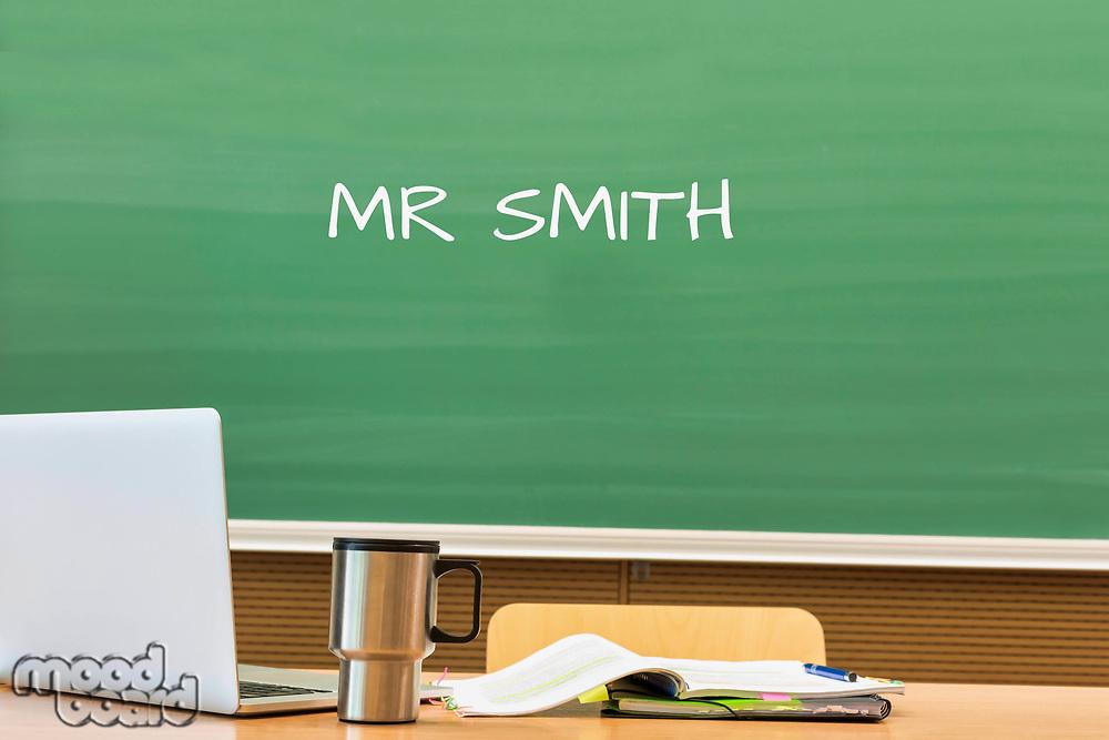 Photo of professor desk in classroom with Mr Smith name written in black board