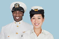 Portrait of multi-ethnic US Navy officers smiling over light blue background