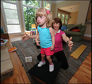 100607 - Smyrna -  Hannah Foy works on her balance under the watchful eye of Sharon Cook ,her physical therapist inside her home on Monday, June 7, 2010.  She is a special needs student at Nickajack Elementary School . Cobb County fired more than 170 special education teachers. It's a move that critics say will harm the most vulnerable students in the county. Of those laid off, 79 were part time. 72 were limited contract and 20 were full time.  They represent about 10 percent of the county's special ed. teachers.  Parents rallied around one pre-K teacher at Nickajack Elementary School who was cut, saying she is the reason their children can walk, talk and learn.<br /> &copy; 2010 JOHNNY CRAWFORD