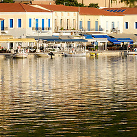 Buildings in the waterfront town of Katakolon reflect in the harbor. The town is a popular docking point for cruise ships whose passengers wish to visit Ancient Olympia.