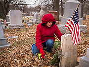 14 DECEMBER 2019 - DES MOINES, IOWA: JILL CURRY, from West Des Moines, places a Christmas wreath on a veteran's headstone. Volunteers working with Wreaths Across America placed Christmas wreaths on the headstones of more than 600 US military veterans in Woodland Cemetery in Des Moines. The cemetery, one of the first in Des Moines, has the graves of veterans going back to the War of 1812.     PHOTO BY JACK KURTZ