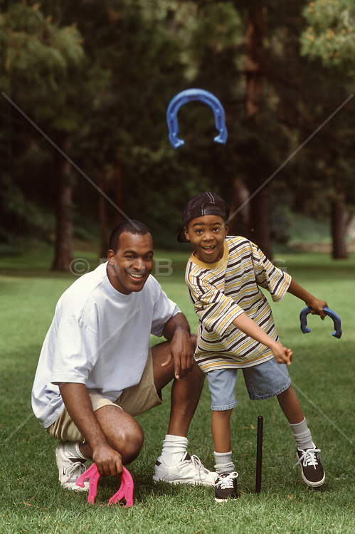 little boy throwing horseshoes with his dad