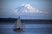 Mount Rainier looms large over a sailboat as seen from the Bainbridge Ferry. (Bettina Hansen / The Seattle Times)