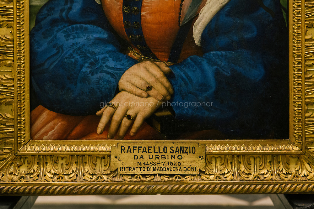 FLORENCE, ITALY - 3 JUNE 2018: A detail of the portrait of Maddalena Strozzi, painted by Raphael, in room 41at the Uffizi, in Florence, Italy, on June 3rd 2018.<br /> <br /> As of Monday June 4th 2018, Room 41 or the &ldquo;Raphael and Michelangelo room&rdquo; of the Uffizi is part of the rearrangement of the museum's collection that has<br /> been defining Uffizi Director Eike Schmidt&rsquo;s grander vision for the Florentine museum.<br /> Next month, the museum&rsquo;s Leonardo three paintings will be installed in a<br /> nearby room. Together, these artists capture &ldquo;a magic moment in the<br /> first decade of the 16th century when Florence was the cultural and<br /> artistic center of the world,&rdquo; Mr. Schmidt said. Room 41 hosts, among other paintings, the dual portraits of Agnolo Doni and his wife Maddalena Strozzi painted by Raphael round 1504-1505, and the &ldquo;Holy Family&rdquo;, that Michelangelo painted for the Doni couple a year later, known as the<br /> Doni Tondo.