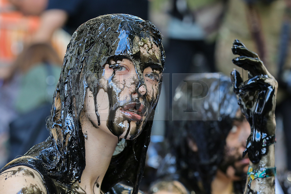 """© Licensed to London News Pictures. 13/09/2019. London, UK. A campaigner from People for the Ethical Treatment of Animals (PETA) protests against the hazardous waste associated with the leather industry are covered in black """"toxic slime"""" on the opening day of London Fashion Week. Photo credit: Dinendra Haria/LNP"""