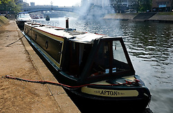 © Licensed to London News Pictures. 21/04/2014<br /> <br /> York, United Kingdom<br /> <br /> The fire on a canal boat smokes in the early morning during warm weather in York.<br /> <br /> <br /> Photo credit : Ian Forsyth/LNP