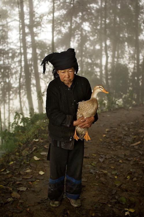 Woman and her duck near Sheng Cun Village in Yuanyang County, China.