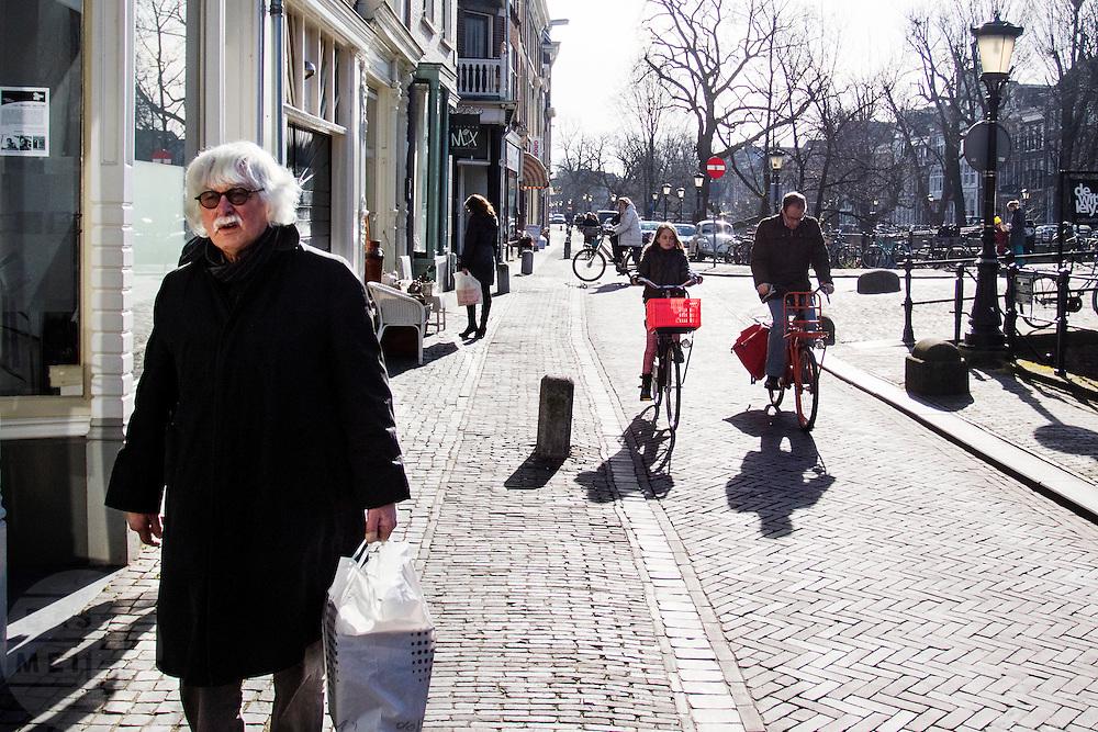 In Utrecht fietst een man samen met zijn dochter door de binnenstad. Een oudere man loopt met een tas met boodschappen.<br /> <br /> In Utrecht a man cycles with his daughter in the city center. An older man is walking with a shopping bag.