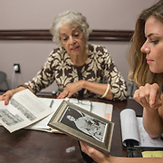 WASHINGTON,DC-AUG21: Kate Billingsley studies a photograph of Sarena (no last name) who is Sheila Thomas' great-great grandmother. Her father is believed to be Roger B. Taney, which would make the former U.S. Supreme Court Justice Sheila's great-great-great grandfather. Roger B. Taney, the U.S. Supreme Court chief justice said blacks had no rights and could not be U.S. citizens. Kate Billingsley is a descendant of Taney, her father is Charles Taney III, a distant nephew of Roger Brooke Taney.  Kate and Sheila would be distant cousins. (Photo by Evelyn Hockstein/For The Washington Post)