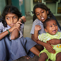 Vijyashree (left) and Vijitha in the family front room with their brother Sanjay. <br /><br />Vijitha and Vijyashree Viswanathan, now age 12 and 10, lost their mother and younger brother to the 2004 Asian Tsunami. The sisters continue to live with their father Viswanathan in a small house in the fishing village of Thalanguda, 5km from Cuddalore. The house does not have a toilet and water is supplied for only a short period of the day. Viswanathan married Kayalvizhi just over a year after the tsunami and the couple now have a son born in December 2006. Of the two sisters it was the elder Vijitha who initially appeared more distressed at her mother's death. But in the subsequent three years she has come to terms with her loss and seems better equipped to face the challenges of growing up without the support of her mother. In contrast Vijyashree, whos younger age may have insulated her from some of the grief experience by her sister, has fallen back in her studies becoming moody, withdrawn and reticent. Vijyashree has suffered fits for a number of years but in the past twelve months these have become more frequent. Viswanathan blames the drugs prescribed to treat his daughter's condition for her moodiness. Another explanation could be the arrival of Vijyashree's half-brother Sanjay with whom she must now compete for the affections of her father. Kayalvizhi does not appear particularly sensitive to the needs of her adopted daughters though her position cannot be easy, particularly when burdened with the task of raising a baby. Viswanathan's sister-in-law Shanthi is especially scathing of Kayalvizhi's indifference to Vijitha and Vijyashree and questions whether the girls should be expected to clean the house, clean utensils and prepare themselves for school. Shanthi complains that the girls must come to her for affection and in the case of Vijyashree this is clearly true. The fervor of Shanthi's condemnation of Kayalvizhi and, by association Viswanathan, could however be