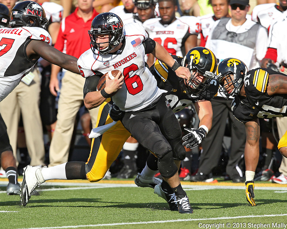 August 31 2013: Northern Illinois Huskies quarterback Jordan Lynch (6) tries to spin away from Iowa Hawkeyes defensive lineman Mike Hardy (98) during the second half of the NCAA football game between the Northern Illinois Huskies and the Iowa Hawkeyes at Kinnick Stadium in Iowa City, Iowa on August 31, 2013. Northern Illinois defeated Iowa 30-27.